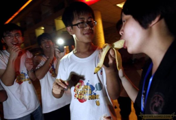 A girl is sucking a banana.
