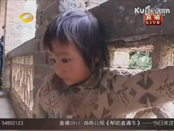A little 3-year-old Chinese girl who stands outside her brother's classroom every day because her family can't afford to send her to school.