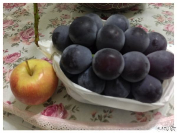 "Lee Kaifu posts on Sina Weibo an image of ""large"" Taiwanese grapes, with an apple next to it for comparison."
