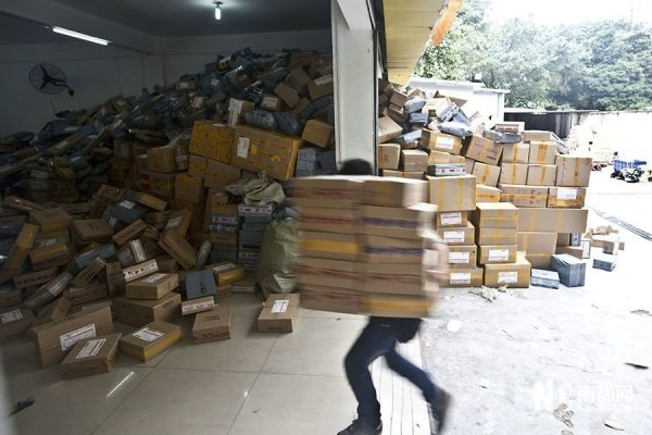 A worker is carrying goods into the warehouse for scanning.