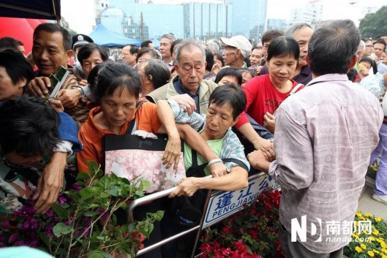 Citizens are fighting for positions in hope of getting potted flowers as soon as possible.