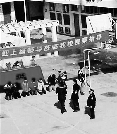 "7 Students Kneeling Down Under A Banner That Says ""the Superior Leaders to Our School"""