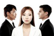 An Asian woman between an Asian man and a non-Asian man.