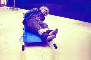 A homeless old man bound lying on a stretcher in the lobby of a rescue shelter in Changsha, begging the reporter for help.