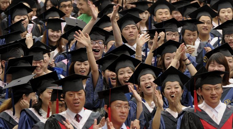 Chinese university students in caps and gowns during a graduation ceremony.