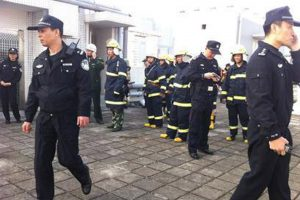 Chinese police officers and firefighters on the roof of an apartment building in Guangzhou following an explosion.