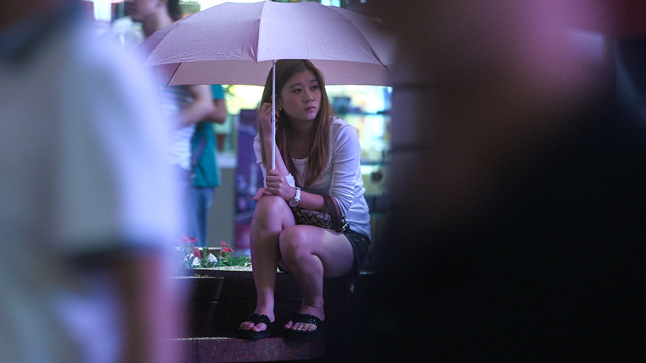 A Chinese girl sitting on the side of the street holding an umbrella.