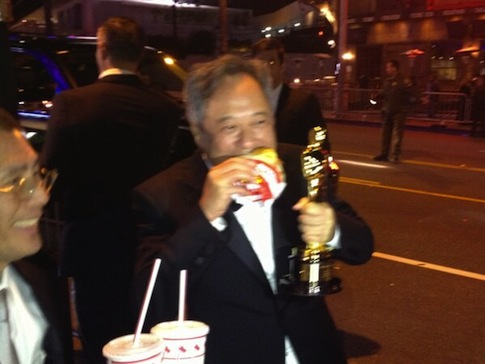Chinese director Ang Lee eating an In-N-Out hamburger after the 85th Academy Awards, while still holding onto his Oscar statuette.