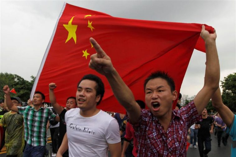 Young male Chinese protesters carrying a flag and pointing a finger forward: Charge!