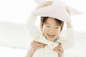 Cute Asian little boy holding pillow.
