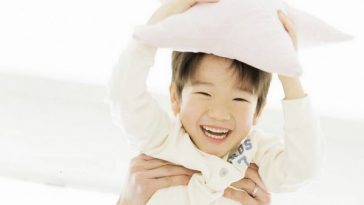 Cute Asian little boy holding pillow.
