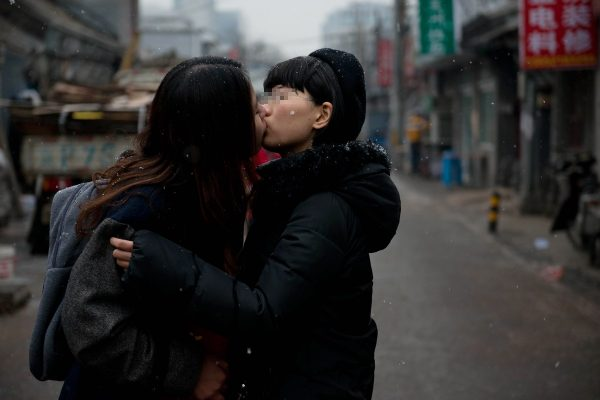 Elsie and Mayu are kissing on the street.