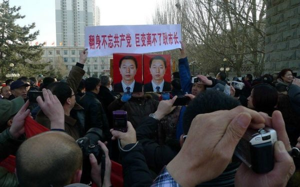 People in parade are carrying slogan and Mayor Geng's picture.