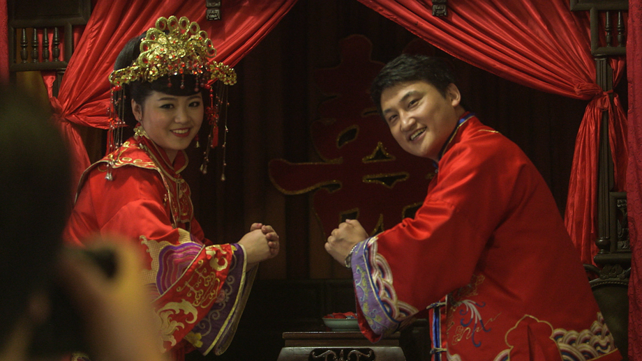 A Chinese wedding couple in traditional wedding costume.