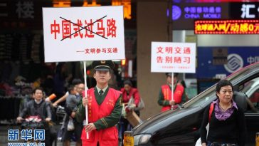 Chinese traffic officials waging a public service campaign against pedestrians crossing streets during red lights.