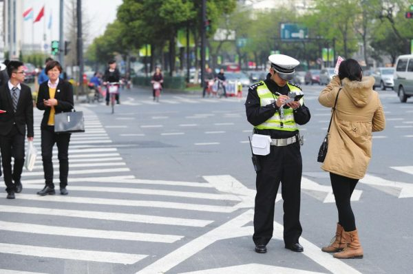 A Chinese police officer giving a ticket and fining a pedestrian who has crossed a street illegally.