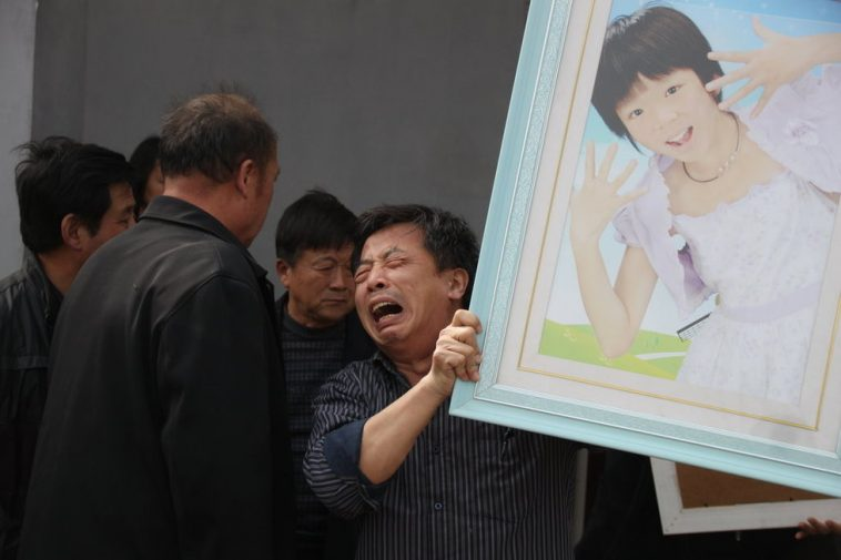Zhao Qi holding her daughter's picture.