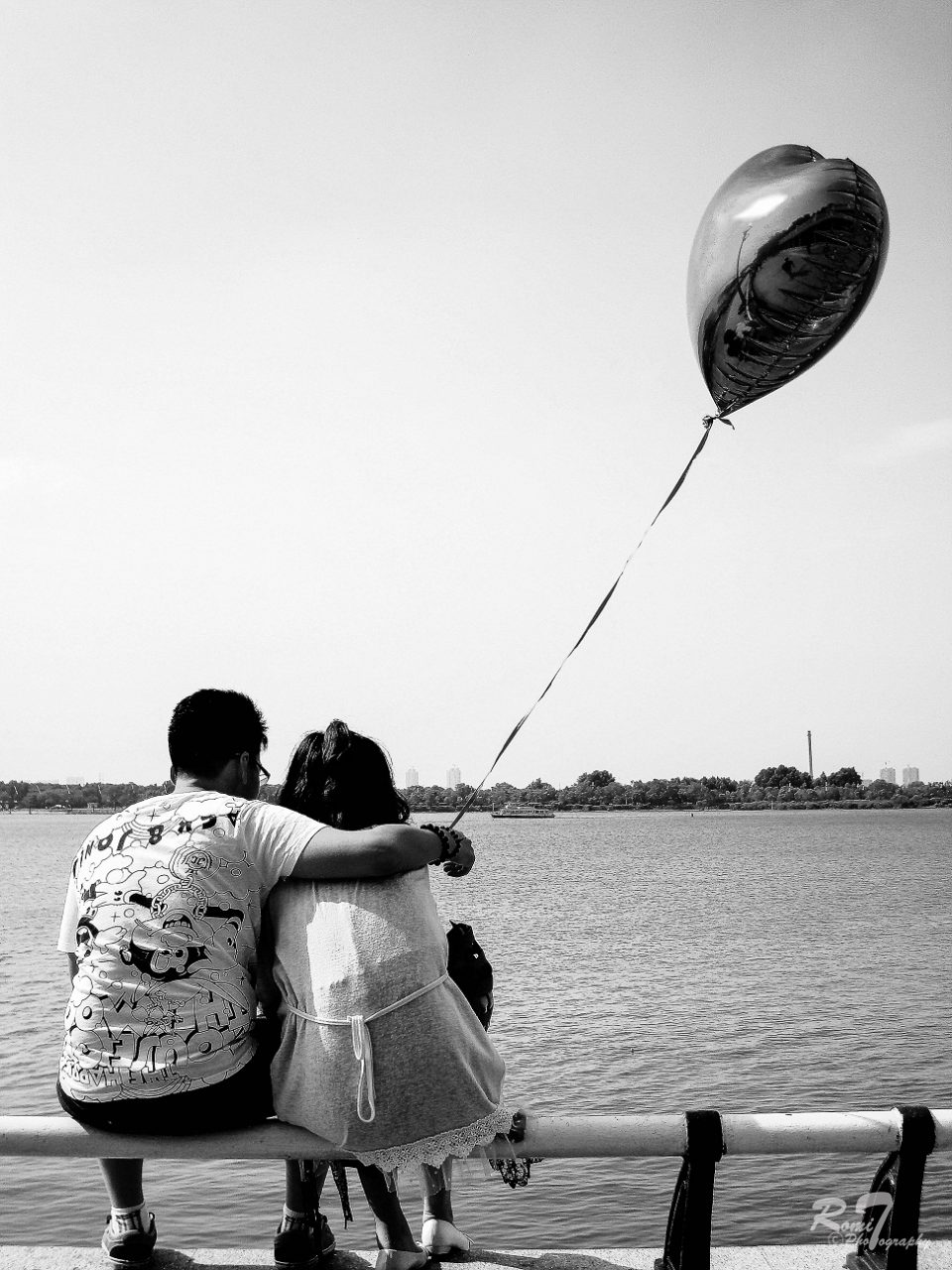 A young couple by the lake with a balloon, by Romit Thapa