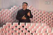 #1 Chinese philanthropist Chen Guangbiao standing amongst stacks of RMB cash bills money.