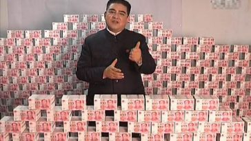 #1 Chinese philanthropist Chen Guangbiao standing amongst stacks of RMB cash bills money.