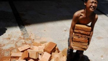 A young Chinese boy carrying bricks.