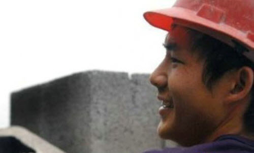 A young Chinese man in a construction hat with cinderblocks in the background.
