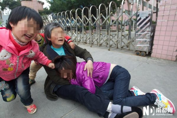 Ms. Hu is crying in her mother-in-law's arms.