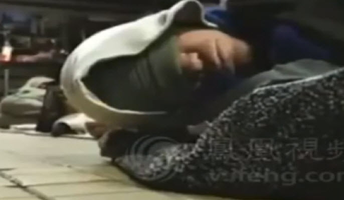 Screenshot of a man sleeping on the ground in a purported North Korean propaganda video about how Americans live today.