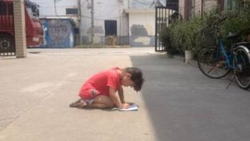 The little girl is doing her homework in the sun.