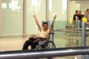 A wheelchair bound Chinese man who was distributing fliers in Beijing International Airport holds up a homemade explosive device.