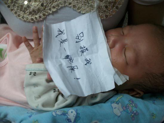 A piece of paper written with dirty words is stuck on the baby's face.