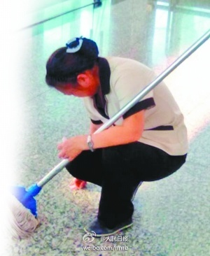 A Chinese female sanitation worker scraping gum off the floor of an airport in China.