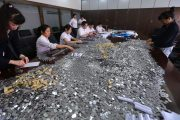 Chinese bank employees counting 1 mao (10 cent) coints.