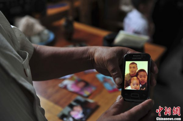 Li Kaihai is looking at a photo of his son and grandchildren.