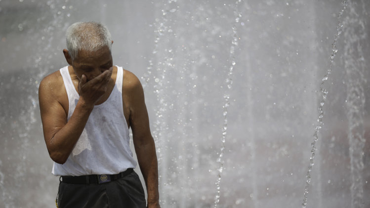 An elderly Chinese man wipes his face with water from a fountain.