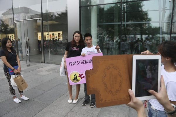 A woman is taking a picture wit the AIDS-infected man.