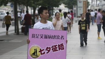 The AIDS-infected man is on the street with a marriage-seeking sign.