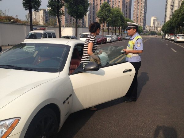 A rich Chinese girl was seen parking her expensive Maserati super car on the double-yellow lines in the middle of the street in Chongqing, despite available parking spaces on the side.