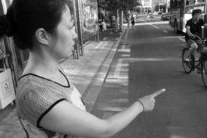Ms. Wang at the bus stop where the elderly person had fallen, describing to this reporter what happened at the time.