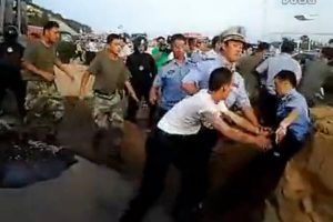 Qingdao, Shandong, screenshots from a video purportedly showing a brawl between China's chengguan city management officers and PLA soldiers over the demolition of a guard building.