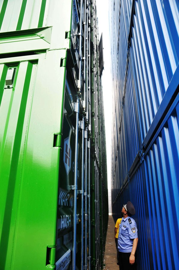 A policeman is looking at the cargo containers.