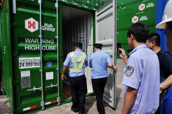 Police officers are opening the cargo container where Jiang was trapped.