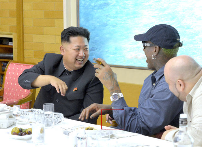 "Kim Jong-un meeting with Dennis Rodman on his second visit to North Korea. A ""third hand"" appears in the photo, believed to possibly belong to an interpreter who was edited out of the photo."