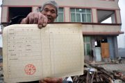 A Chinese man holds up his real estate certificate in front of a nail house in China.