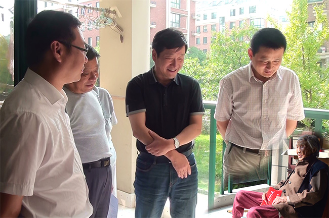 Chinese government officials visit a 103-year-old centenarian in Anhui Ningguo, and become an internet sensation due to one image that was photoshopped so they appear to be floating.
