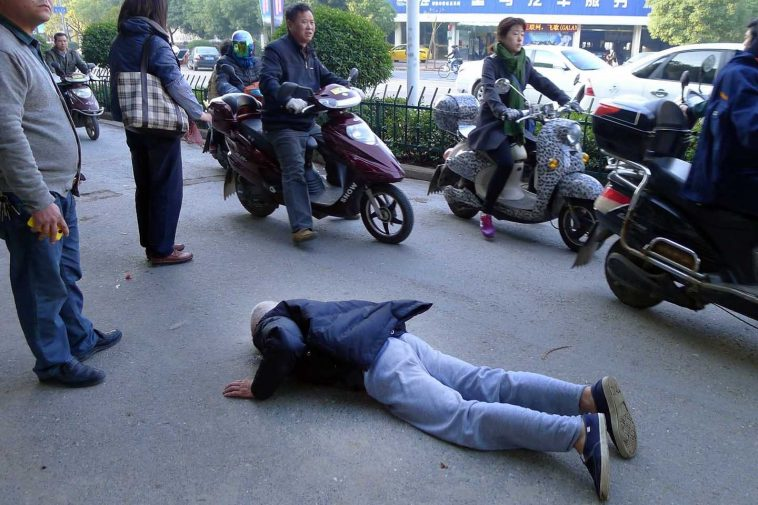 An 80-year-old elderly man in Zhejiang, China who had fallen. Bystanders helped redirect traffic around him but dared not help him up themselves, instead calling an ambulance and police.