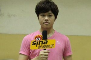 Li Tianyi holding a microphone for Sina Entertainment.