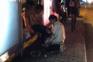 A Chinese schoolboy in Suzhou woos a fellow classmate at a bus stop with a love letter and getting donw on his knees.