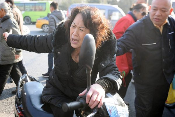 Photo of middle-aged woman clinging to the British foreigner's motorscooter refusing out of fear that he might flee the scene.