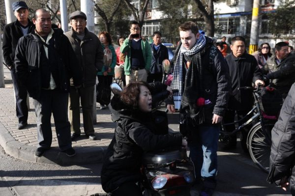 A middle-aged Chinese woman clutches to a British foreigner in Beijing claiming injury and demanding compensation after a traffic accident.